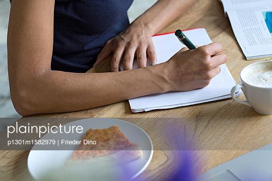 Frau schreibt Notiz am Schreibtisch auf dem auch ein Stück Pizza liegt - p1301m1582979 von Delia Baum