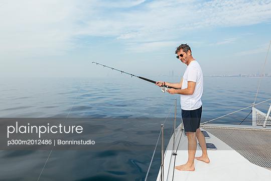 Mature man standing on catamaran, fishing - p300m2012486 von Bonninstudio
