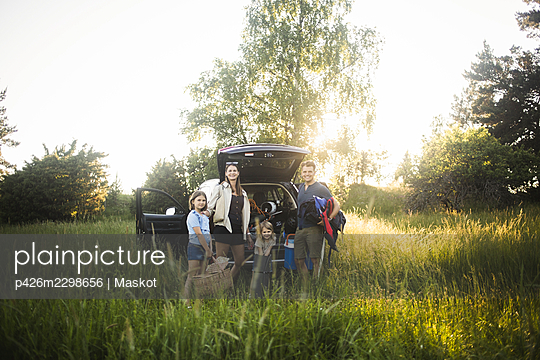 Portrait of mother, father and two daughters standing by car at electric vehicle charging station - p426m2298656 by Maskot