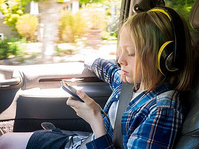 Boy looking at mobile phone while listening music in car - p1166m1541832 by Cavan Social