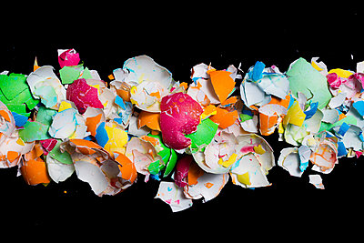 Overhead view of broken colorful Easter eggs on black background - p1166m1556296 by Cavan Images