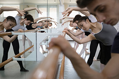 Focused ballet dancers practicing at barre in dance studio - p1192m1403459 by Hero Images