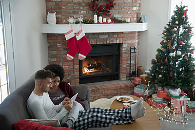Young couple in pajamas relaxing on sofa near fireplace in Christmas living room - p1192m1512225 by Hero Images