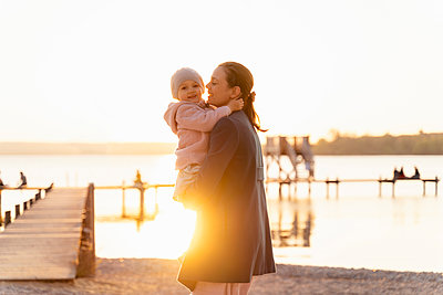 Germany, Bavaria, Herrsching, mother carrying daughter at the lakeshore at sunset - p300m2102589 by Daniel Ingold