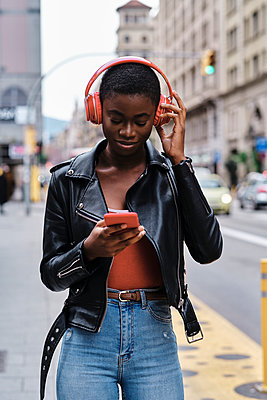 Woman listening music through headphones while using smart phone standing in city - p300m2250268 by Alvaro Gonzalez