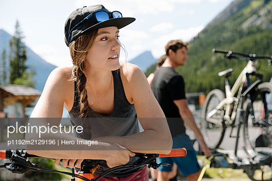 Woman leaning on mountain bike - p1192m2129196 by Hero Images