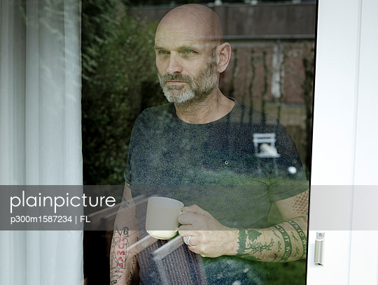 Tattooed man drinking coffee, looking out of window - p300m1587234 von FL photography