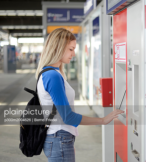 Blond woman using ticket machine at train station - p300m2004626 von Bernd Friedel