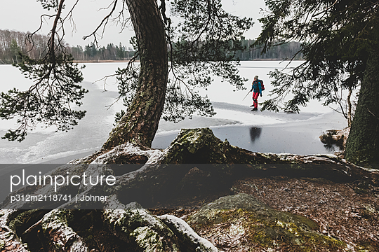 Ice skater on frozen lake - p312m2118741 by Johner