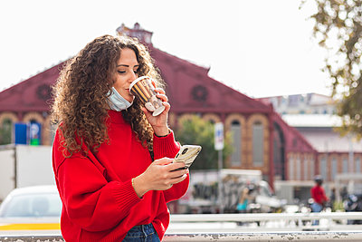 Young woman drinking coffee while using mobile phone in city during COVID-19 - p300m2241056 by NOVELLIMAGE