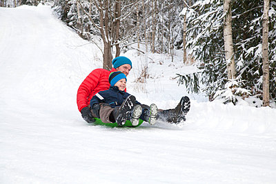 Man and son tobogganing down hill in snow covered forest - p924m1513413 by Tiina & Geir