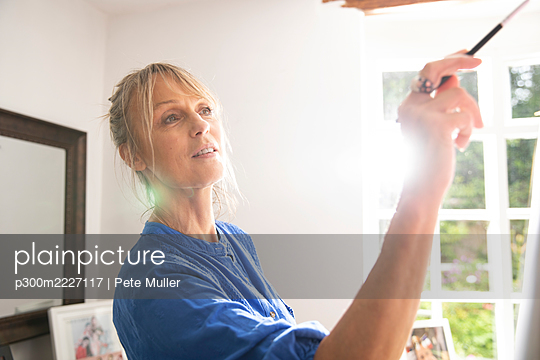 Senior woman painting at home on sunny day - p300m2227117 by Pete Muller