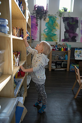 Preschool girl reaching for markers on shelf in classroom - p1192m1560107 by Hero Images
