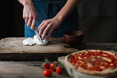 Young man preparing pizza, cutting mozzarella on chopping board - p300m2083098 von Alberto Bogo