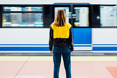 Rear view of a young woman standing on underground station platform - p300m2144056 by Jose Luis CARRASCOSA