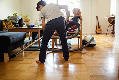 Boy cleaning floor with vacuum cleaner while mother sitting on armchair at home - p426m1192999 by Maskot