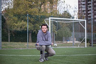 Caucasian man crouching on soccer field in urban park - p555m1412367 by Alberto Guglielmi