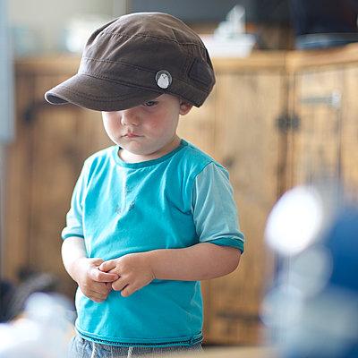 Kleiner Junge schmollt unter Cappy - p606m1564848 von Iris Friedrich