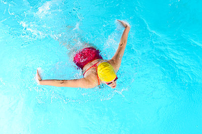 Mature woman doing butterfly stroke in swimming pool - p924m807063f by Pete Saloutos