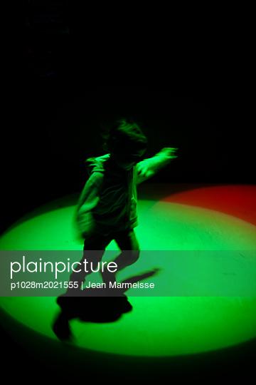Young boy playing under spotlights - p1028m2021555 von Jean Marmeisse