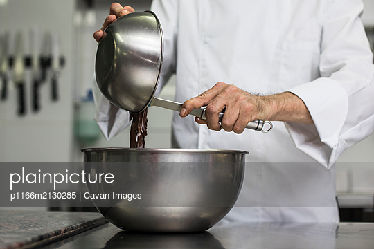 Chef pouring chocolate mass into mixing bowl - p1166m2130285 by Cavan Images