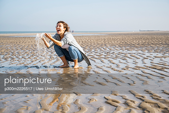 Cheerful young woman playing with water at seashore - p300m2226517 by Uwe Umstätter