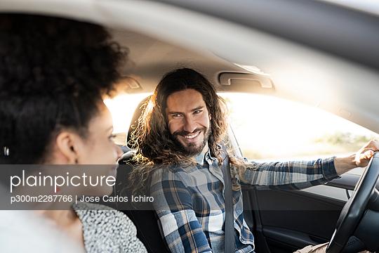 Smiling boyfriend looking at girlfriend while driving car - p300m2287766 by Jose Carlos Ichiro