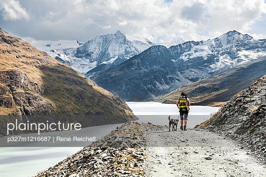 Frau mit Hund unterwegs in den Bergen - p327m1216687 von René Reichelt