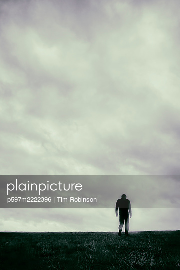 Rearview blurred man walking on grass field - p597m2222396 by Tim Robinson