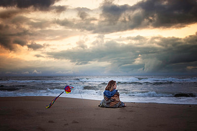 Girl looking at view while being wrapped in blanket on shore against stormy clouds - p1166m1509613 by Cavan Images
