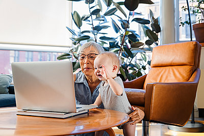 Senior woman sitting with granddaughter using laptop to video call - p1166m2285625 by Cavan Images
