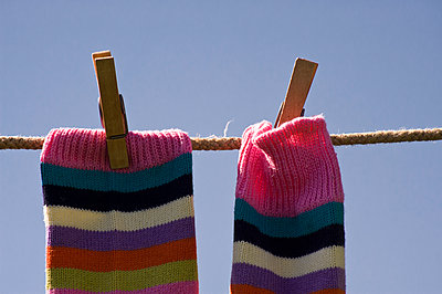 A pair of colourful, stripy socks clipped onto a washing line. - p1433m1531929 by Wolf Kettler