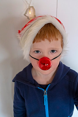 Boy wearing christmas cap and false nose - p236m2064780 by tranquillium