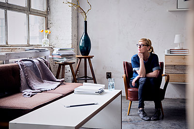 Pensive woman sitting on arm chair in loft looking through window - p300m2030197 by Rainer Berg