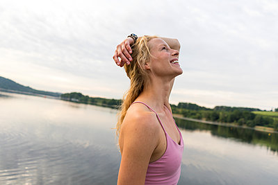 Happy young woman at a lake - p300m2140102 by Joseffson