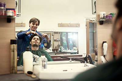 Reflection of barber cutting hair of male customer - p300m2273552 by LOUIS CHRISTIAN