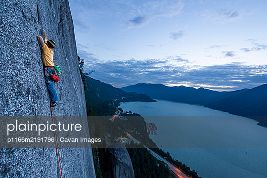 Side view man rock climbing at sunset above the sea and highway - p1166m2191796 by Cavan Images