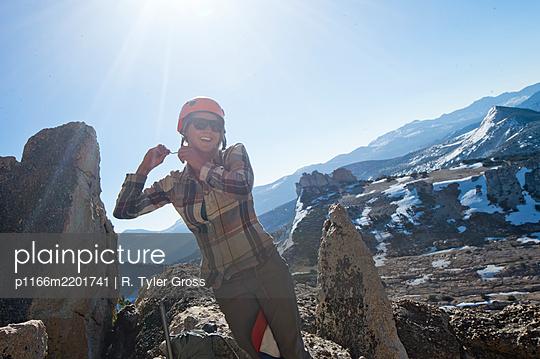 Woman putting on climbing helmet,TuolumneMeadows, Yosemite National Park,California, USA - p1166m2201741 by R. Tyler Gross