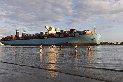 Kinder am Elbstrand mit Containerschiff - p076m2014661 von Tim Hoppe