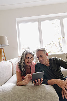 Happy senior couple relaxing on couch at home using tablet - p300m2156236 by Gustafsson