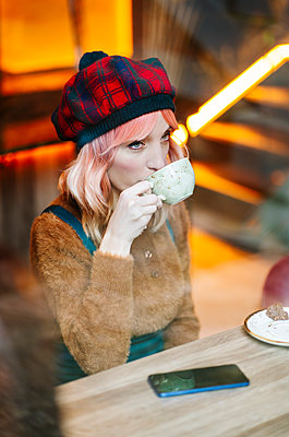 Young woman sitting in restaurant, drinking coffee - p300m2180426 by Daniel González