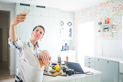 Female freelancer video blogging through smart phone while carrying daughter in kitchen at home - p426m2116967 by Maskot