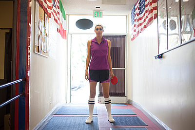Table tennis player standing in corridor of sports centre - p429m1158533 by Raphye Alexius