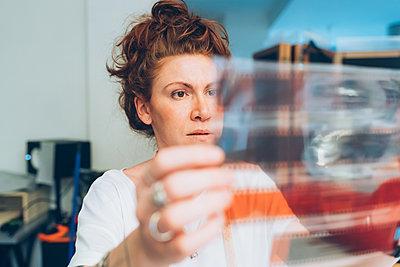 Fashion designer looking at film negative - p429m2058386 by Eugenio Marongiu
