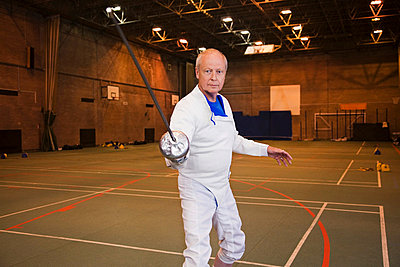 Senior man in fencing suit holding foil - p92411228f by 3rd of May Productions
