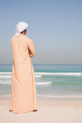 Middle Eastern man standing on the beach - p9244758f by Image Source