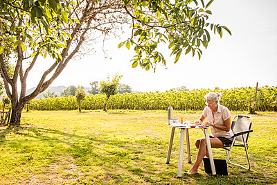 Frau sitzt am Campingtisch und schreibt - p948m2142125 von Sibylle Pietrek