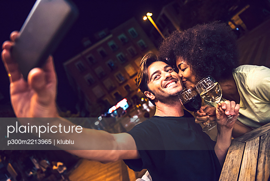 Woman kissing boyfriend taking selfie at date night - p300m2213965 by klublu