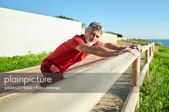 Spain, Andalusia, El Puerto de Santa Maria, man doing stretching in park, looking at camrera. - p300m2275600 von Kiko Jimenez