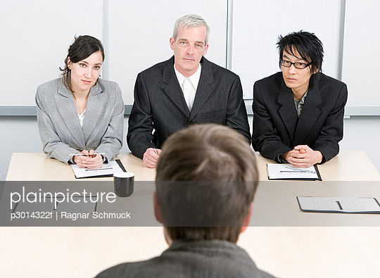 Three people interviewing a job applicant